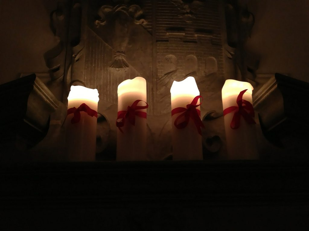 four candles with ribbons